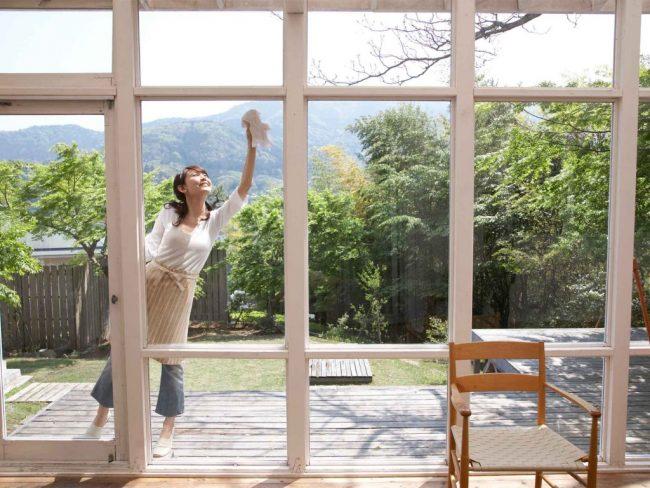 Chica limpiando los cristales de las ventanas